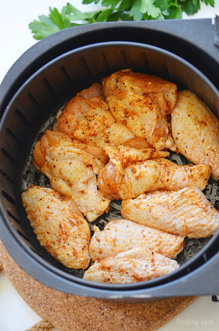 Chicken wings in air fryer basket with dry rub