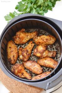 Lemon Pepper Wings Cooking in Air Fryer Basket
